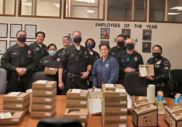 group of many police persons in front of a table full of Urth Lunch Boxes and coffee