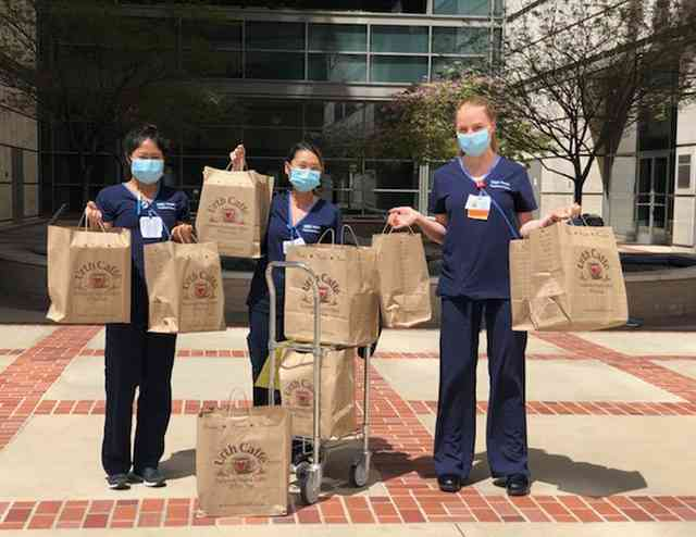 Three nurses with blue masks standing in front of the Ronald Reagan UCLA Med center holding multiple large Urth food bags and a cart with bags in hospital courtyard.