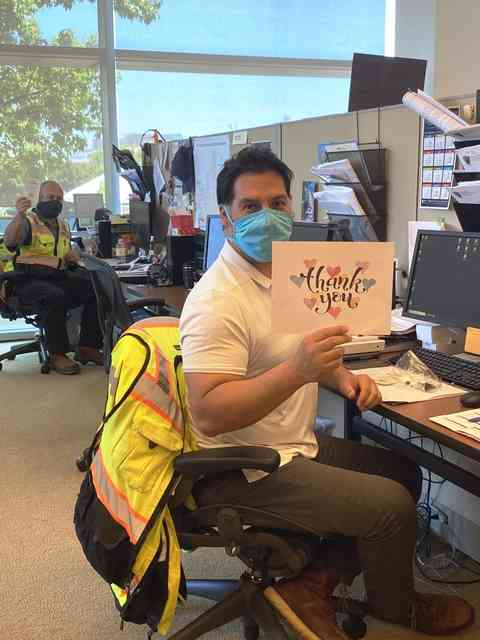 """Man sitting at desk with mask and holding a thank you sign. In the background is another man is sitting at another desk with mask and holding the Urth Caffe """"To Our Brave Heroes"""" card."""