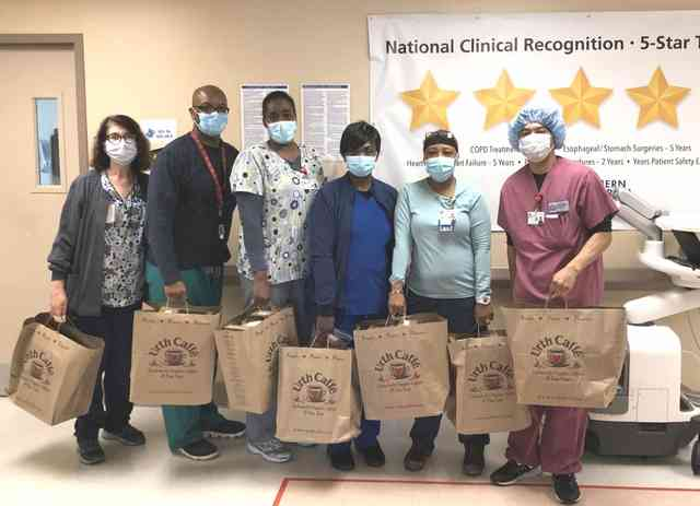 Six nurses in a line holding Urth food bags