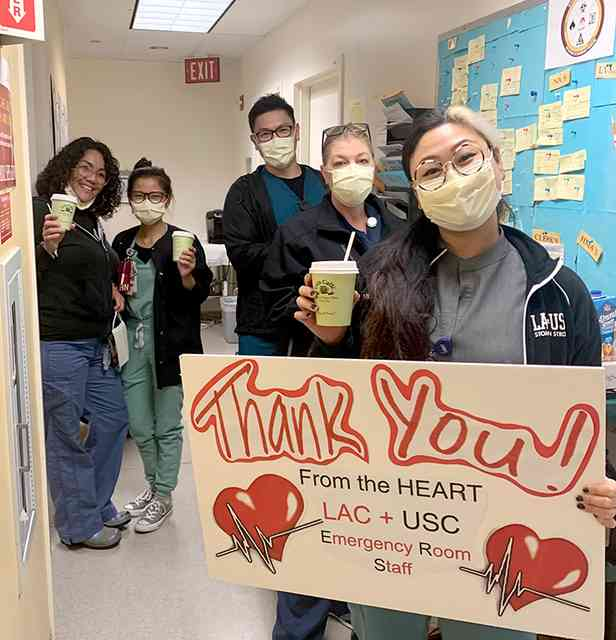 Five nurses standing in a hospital hallway wearing yellow medical masks and holding a green Urth Caffé coffee cups. Front nurse is holding a sign with two big red hearts that reads: Thank You! From the HEART LAC + USC Emergency Room Staff.