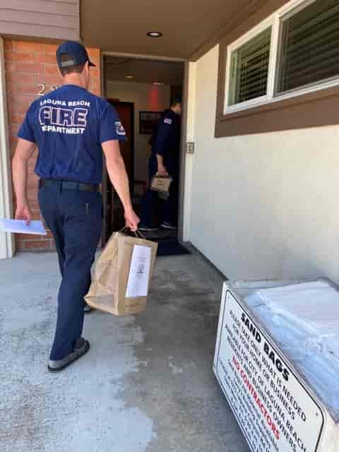 Laguna Beach fireman in t-shirt carrying Urth food bag into station