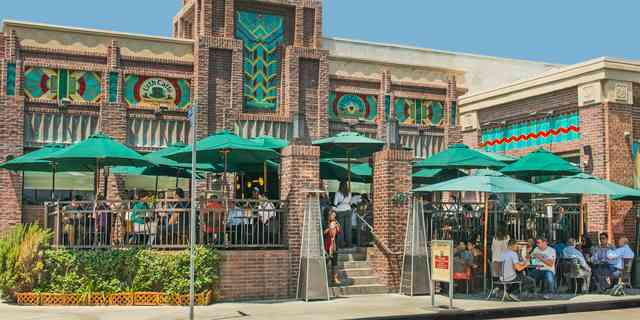 Urth Downtown facade with patios and street side tables full with patrons