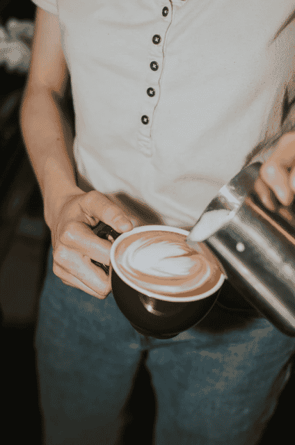 person pouring latte