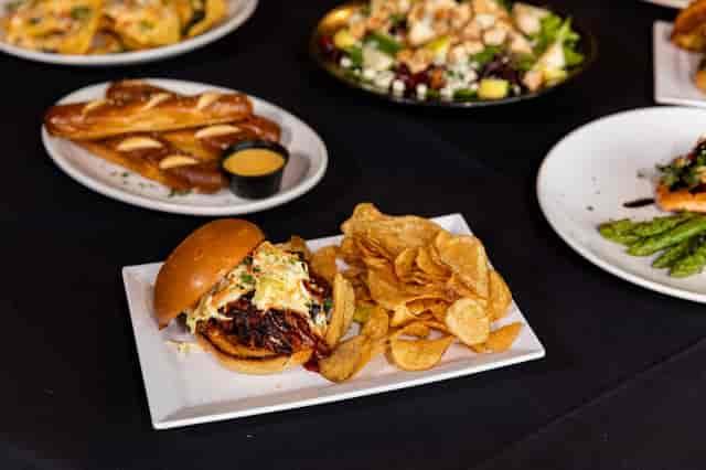 several plates of food including burger, breadsticks, salad