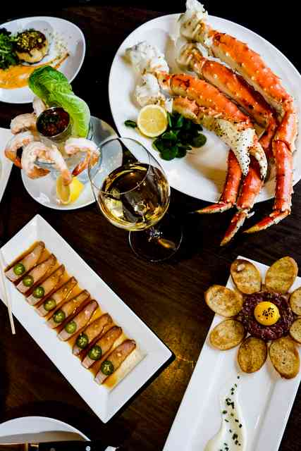 crab legs and appetizers on dark wood table
