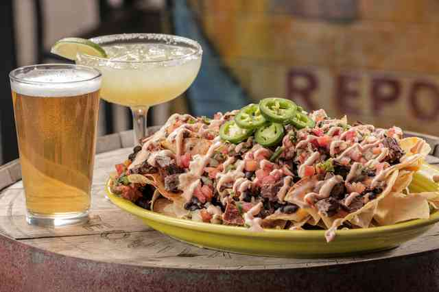 nachos made with homemade chips topped with melted cheddar cheese, black beans, pico de gallo, chipotle crema, and jalapenos. Served along side with a cold beer and Cien-A-Rita.