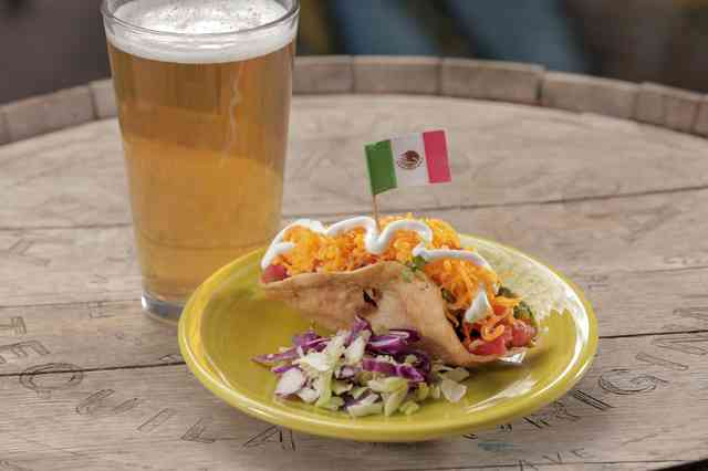 Our most popular taco! Tinga taco, topped with cheddar cheese, lettuce, tomato and crema. Served along side with a beer.