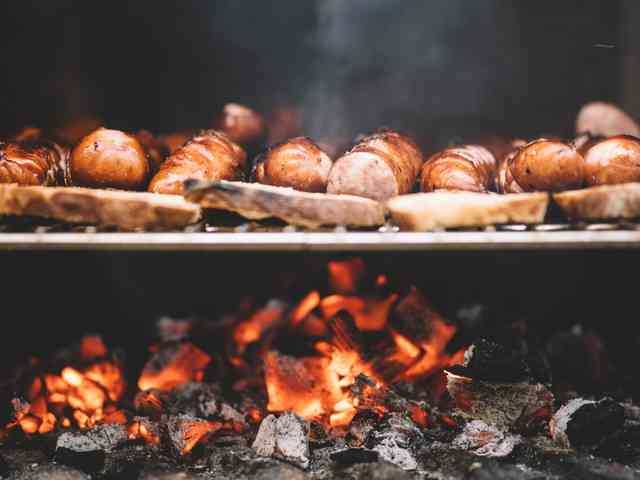 Variety of meats on a grill above a bed of hot coals