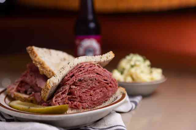 corned beef sandwich with potato salad and a soda