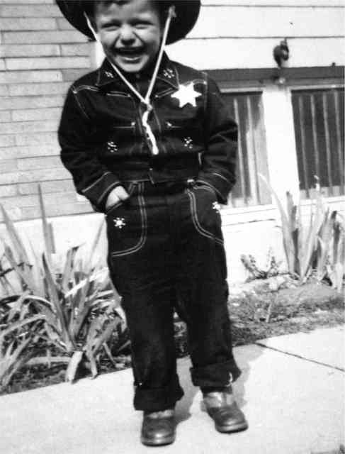 old black and white photo of Comella's family member boy dressed in a cowboy sherrif's costume