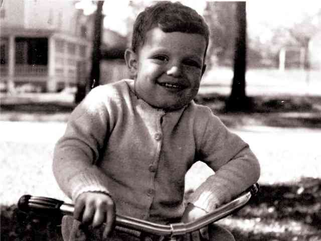 old black and white photo of Comella's family member a boy on a bike