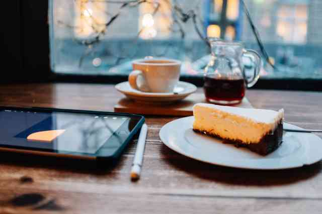 Cake at table with coffee, pen and tablet