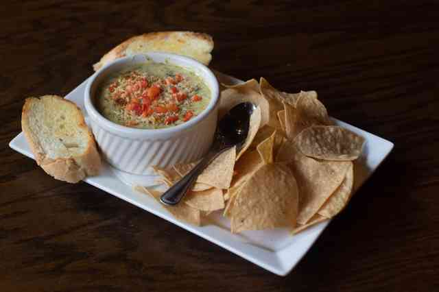 Tortilla chips and slices of bread with spicy spinach artichoke dip