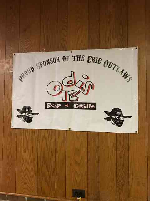 sponsor of eerie outlaws sign posted on wooden wall