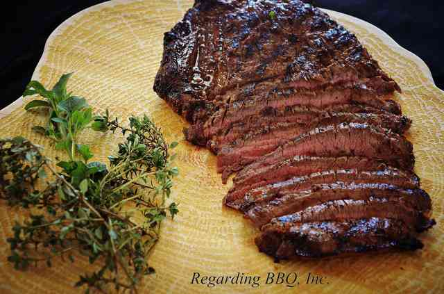 steak on cutting board with herb garnish