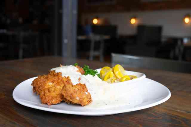 Country fried pork chop with mashed potatoes, stewed squash and sawmill gravy