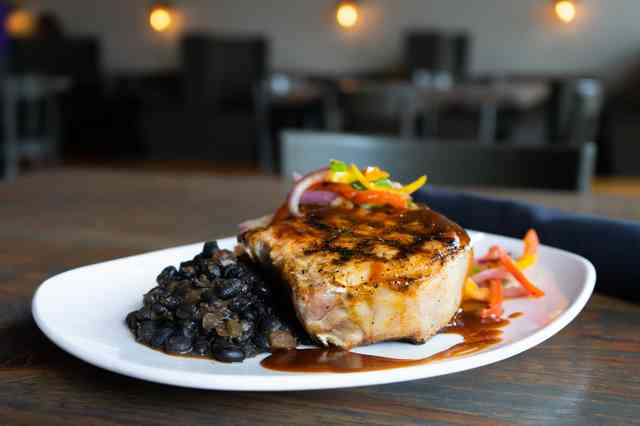 White Marble Farms double-cut Pork chop with chipotle mashed potatoes, black beans, and a pepper medley