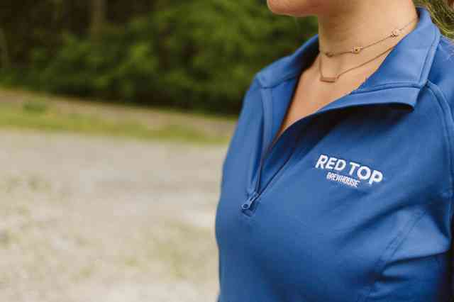 Blue pullover with white wordmark in left breast