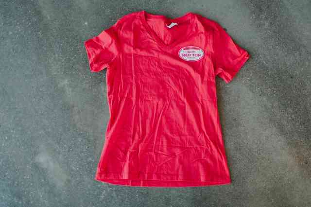 Women's cut red tee with small white oval logo on upper left