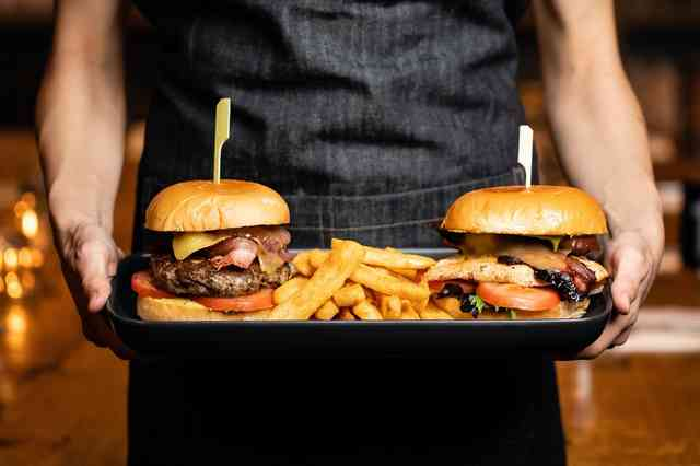 Two burgers and fries carried on a serving tray