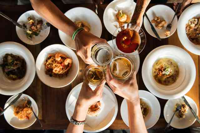 Multiple dishes on a table with a group toasting with various drinks