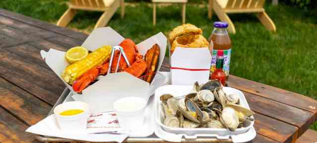 lobster, corn, onion rings, and mussels on a wooden picnic table