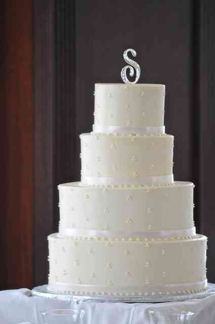 white cake with ribbons and the letter s