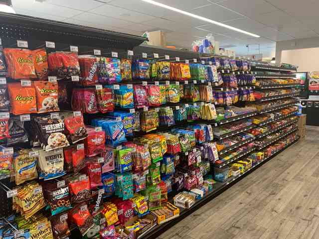 convenience store aisle with clothing items and fishing gear