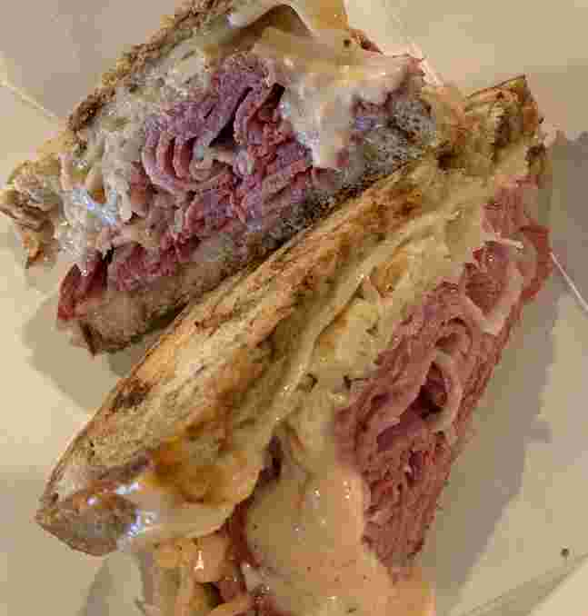 Reuben sandwich-sliced corned beef between marble rye bread with 1,000 Island Dressing and gruyere cheese