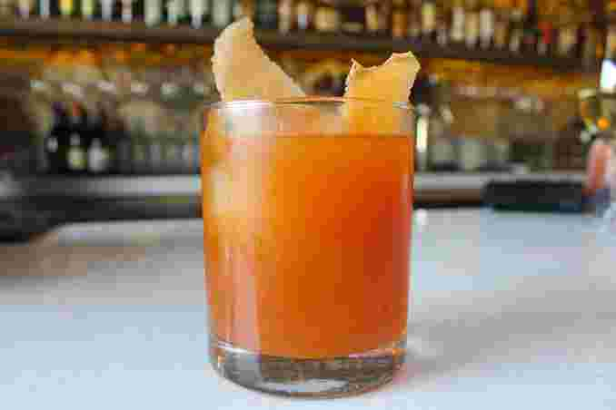 Side close up view of a deep orange craft cocktail