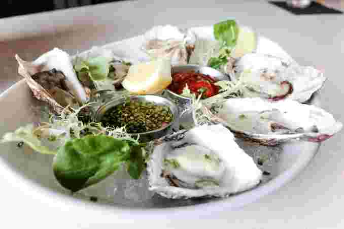 Close up of oysters on a white dish with sauces in the middle