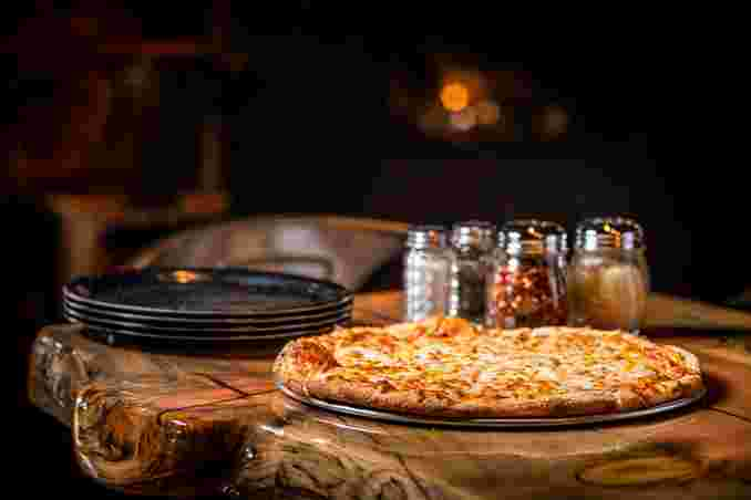 Pizza on table with various shakers of salt pepper parmesan cheese