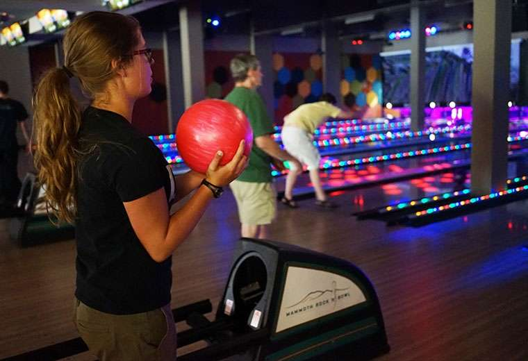 Girl holding a pink bowling ball during cosmic bowling