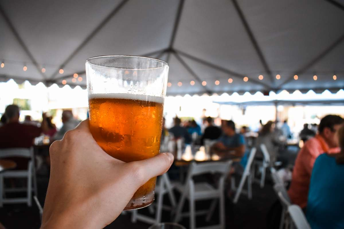 Photo of a hand holding a draft beer with an entertainment tent in the background