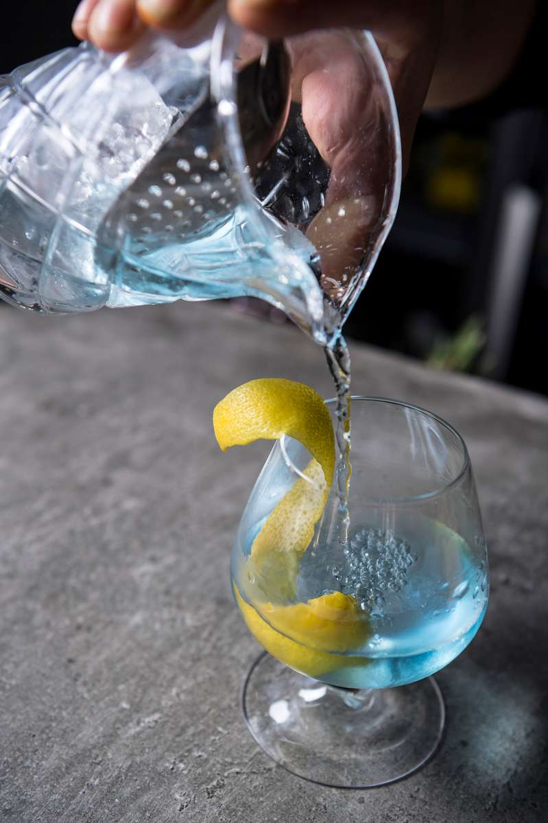 pouring a cocktail from a pitcher