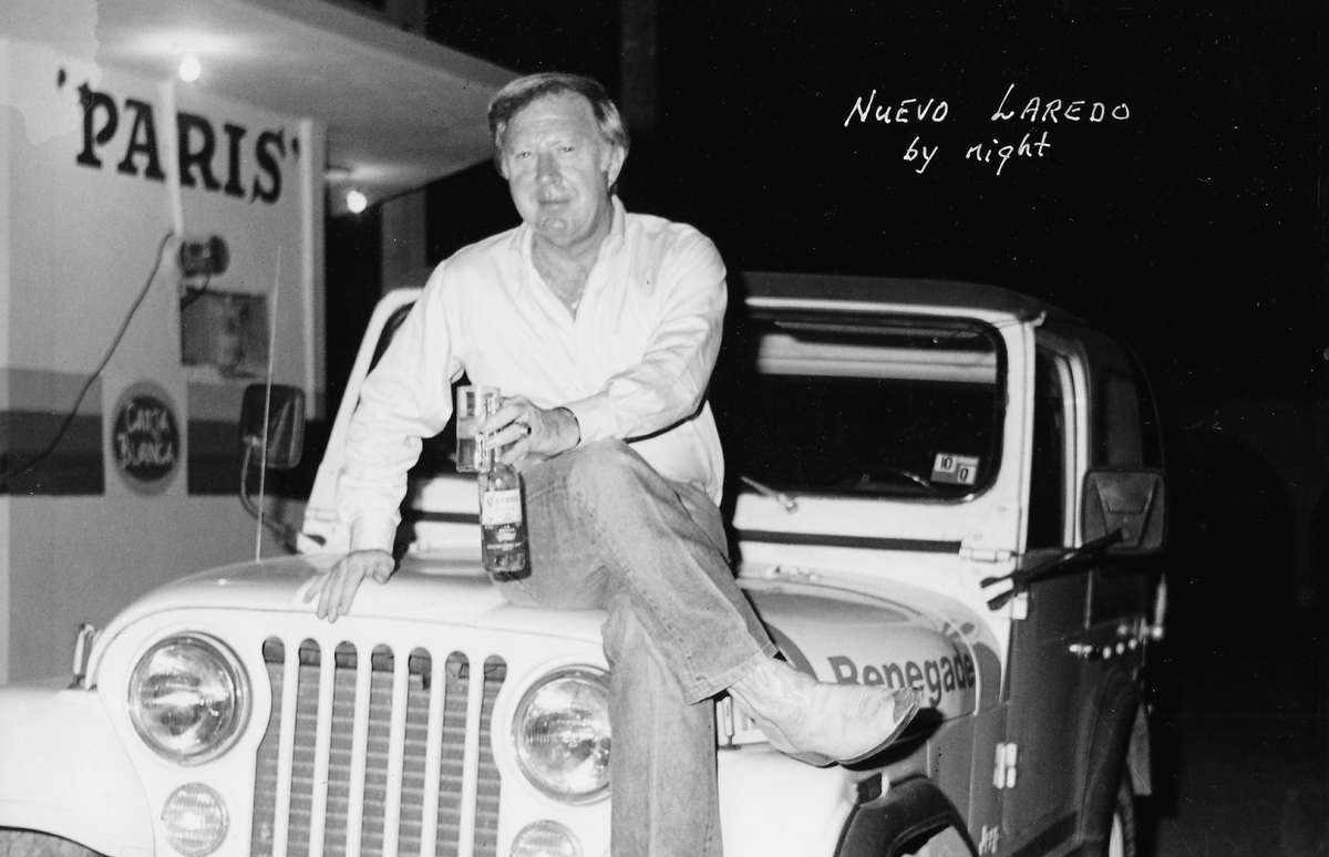 black and white image of a man on a car