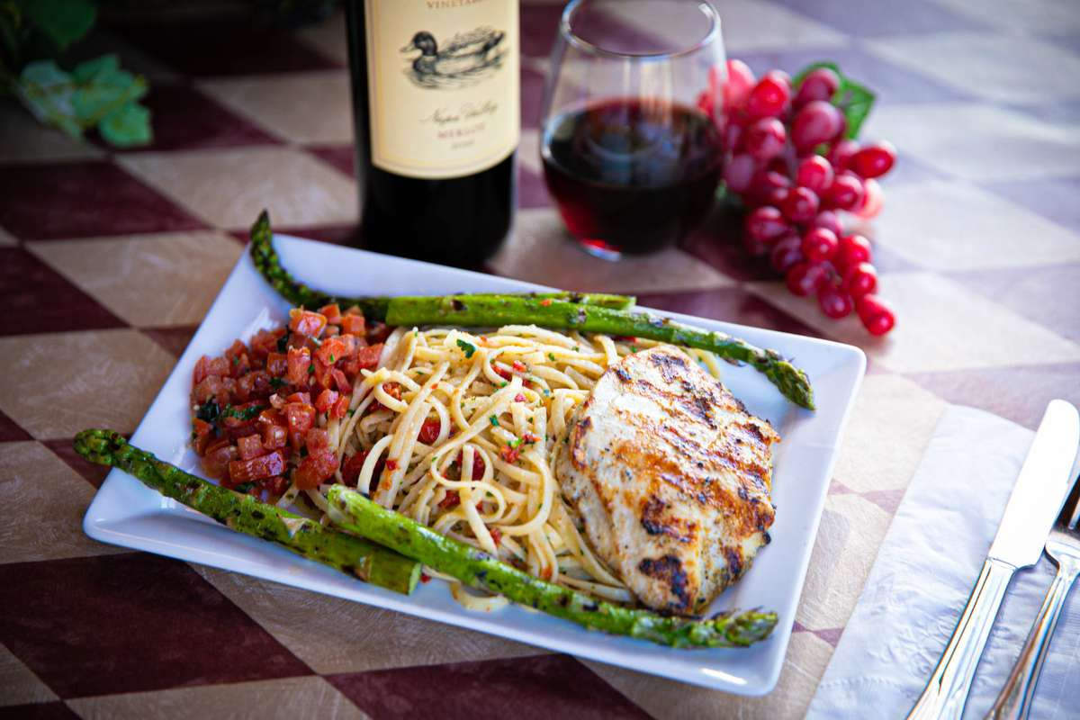 rectangular plate of food with grilled veggies, pasta, and chicken