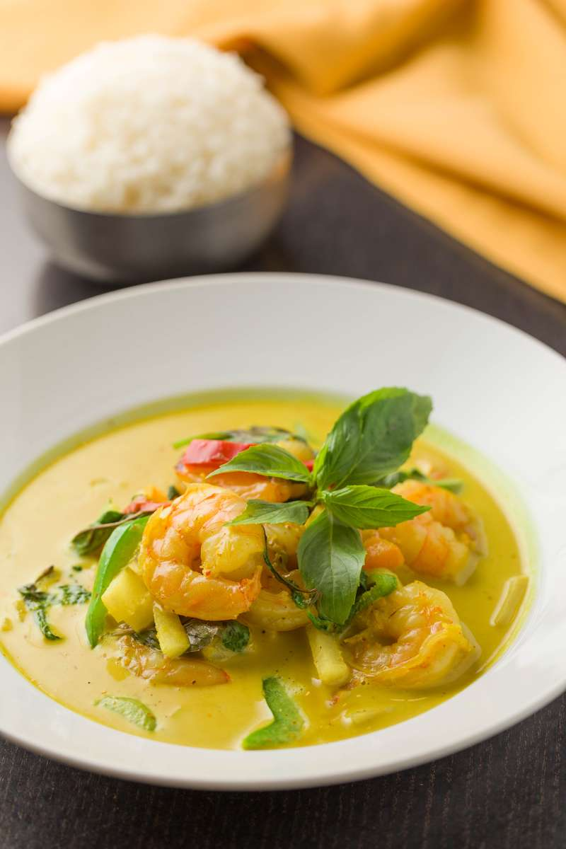 prawn green curry with vegetables and basil garnish