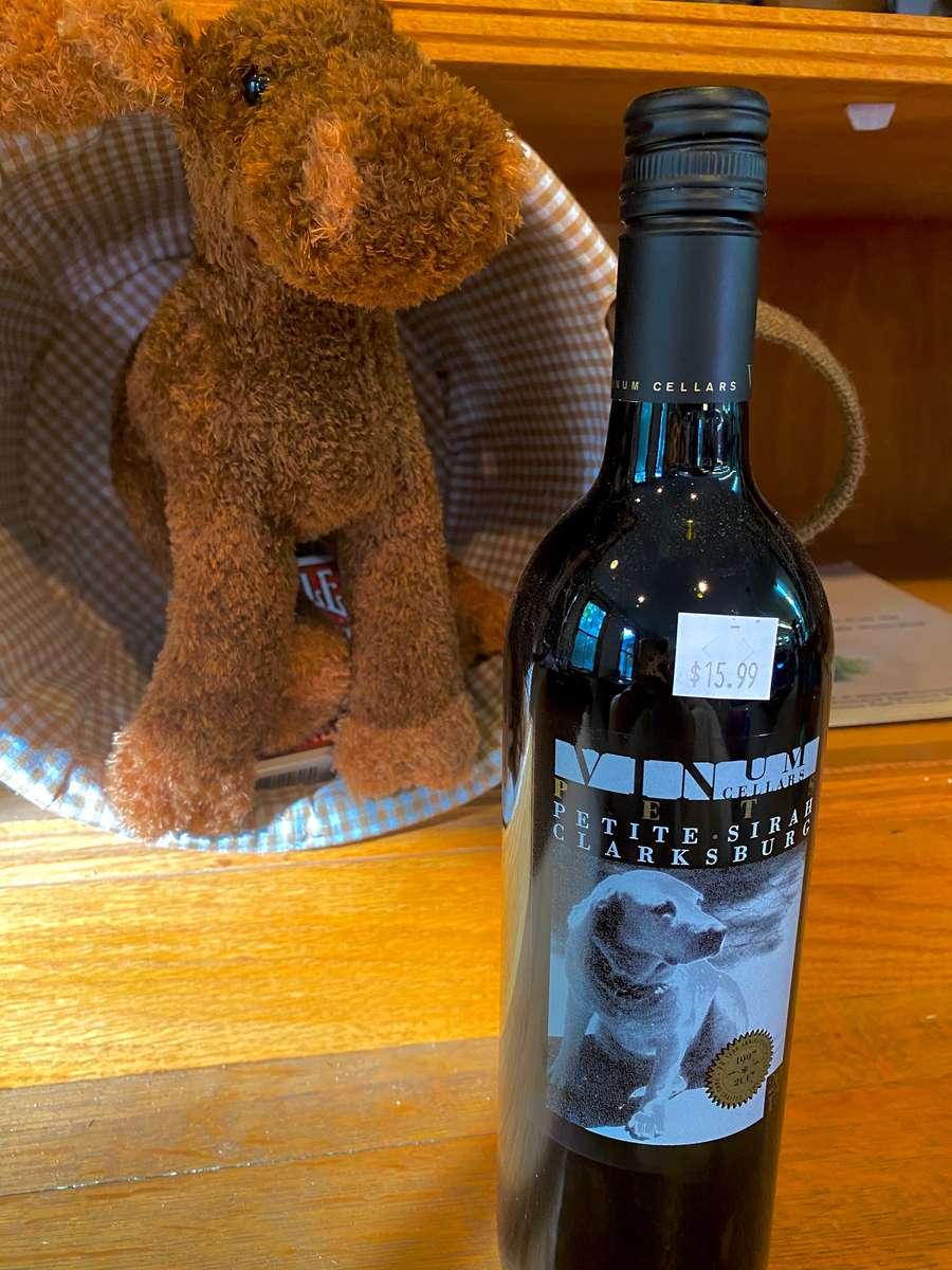 Wine beside a brown moose stuffed toy
