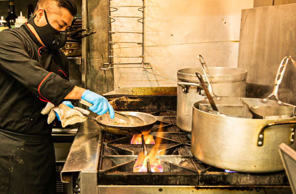 Staff cooking over an open flame