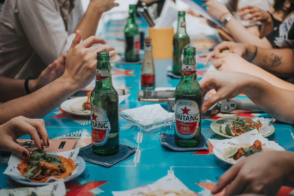 people sitting at table with beer bottles and tacos