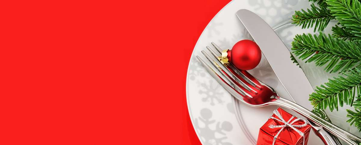 dinner plate with utensils and christmas decor on red background