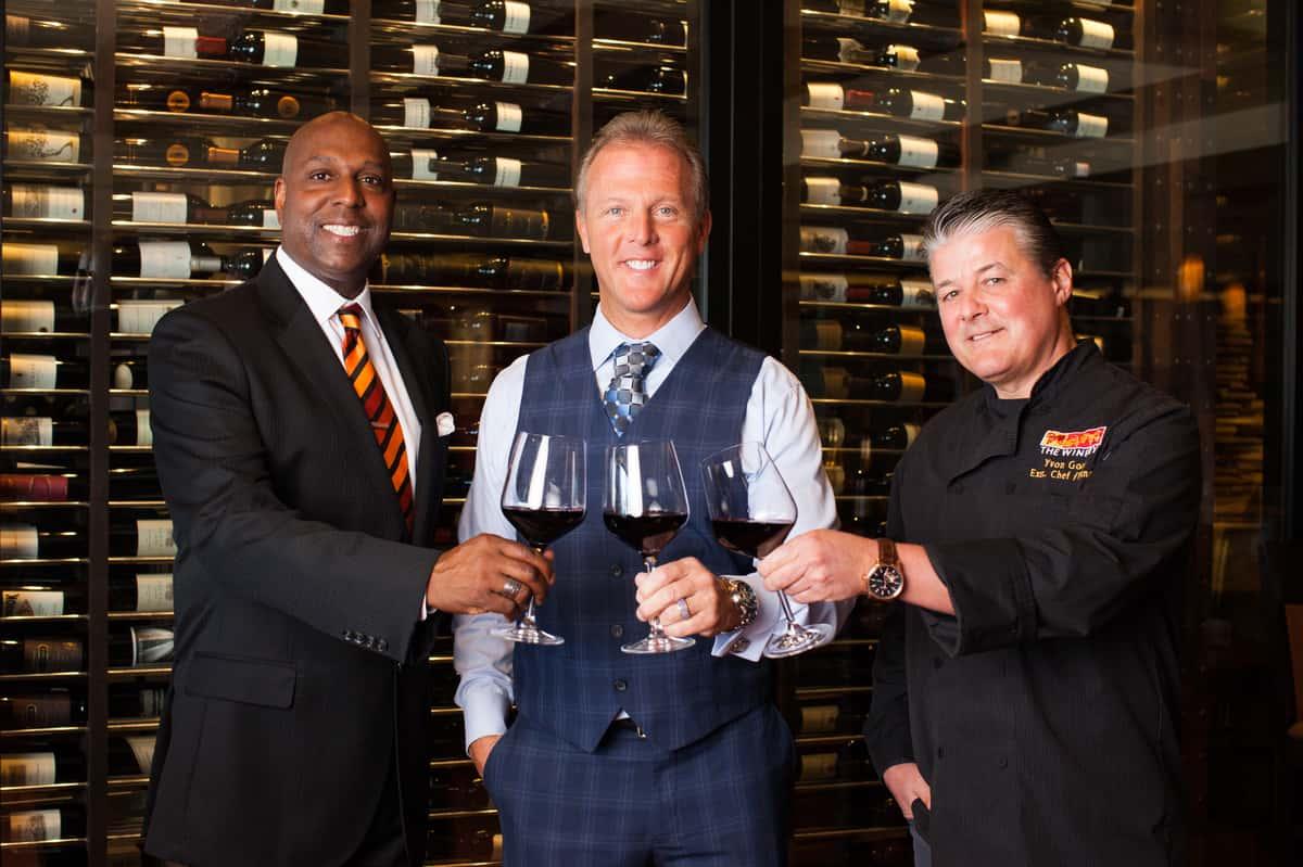 three men holding wine glasses