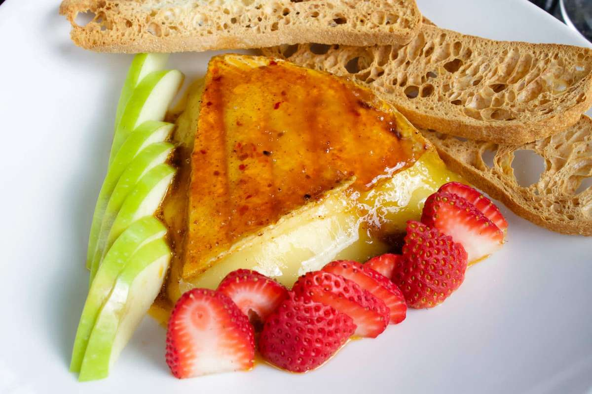 Harissa-Rubbed Baked Brie rubbed with traditional Middle Eastern spices served with tart apple slices, strawberries and crostini