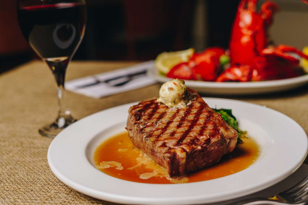 steak with broiled lobster in background