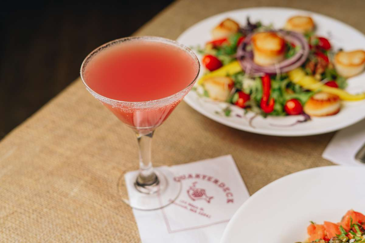 grapefruit martini with scallop salad in background