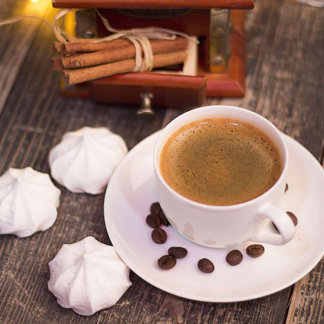 An image of a cup of coffee on a wooden table