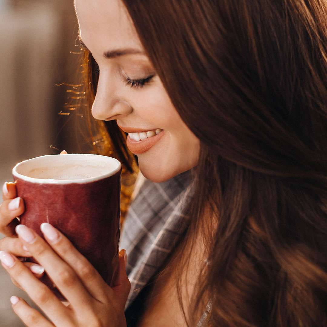 Image of a smiling woman drinking a cup of coffee
