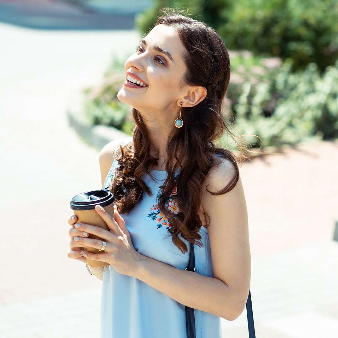 An image of a woman outside in the sun smiling and holding coffee in a to go cup